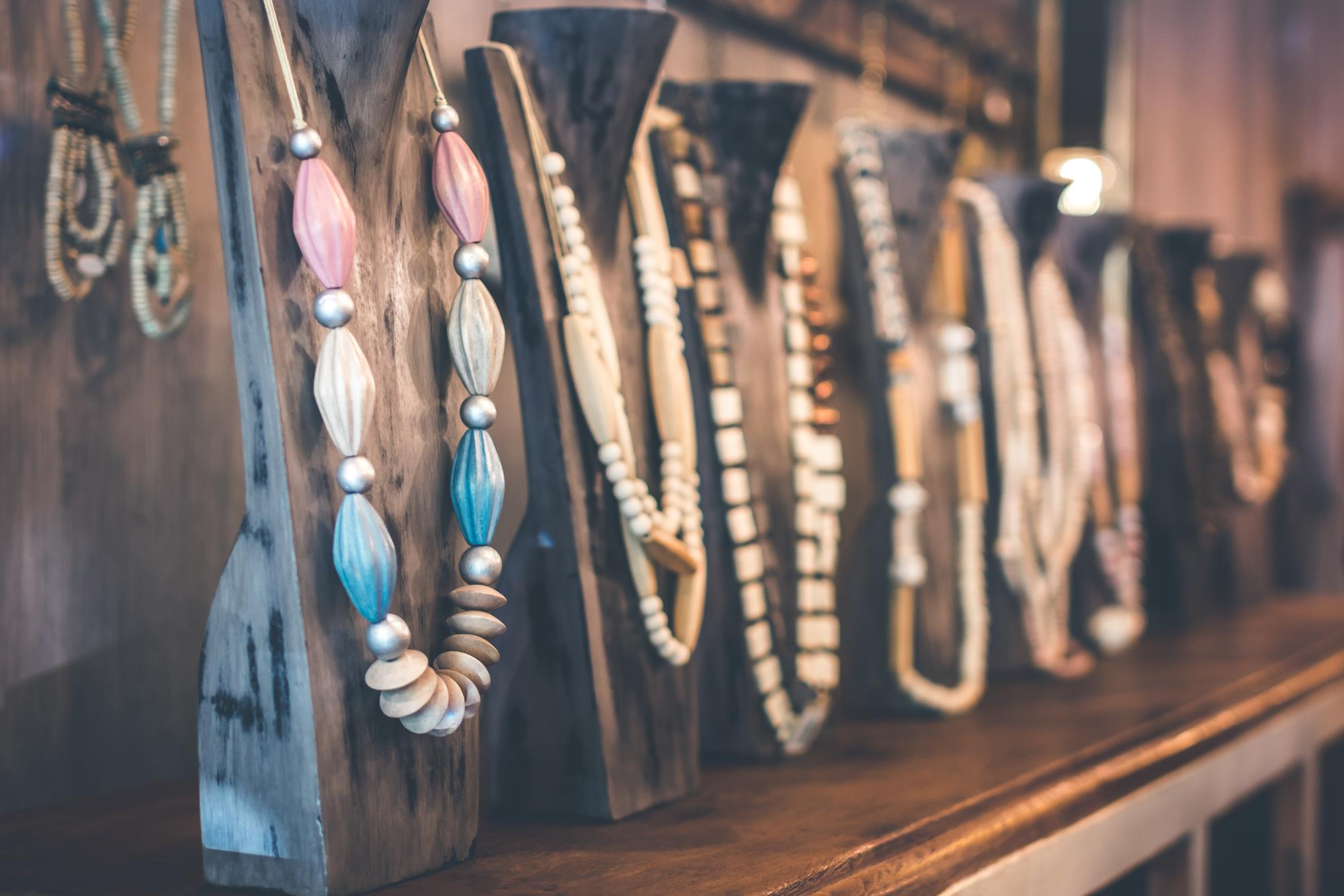 Row of hand-made necklaces on a store shelf